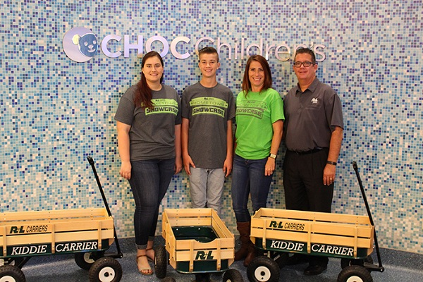 Raymond, a sales representative of R+L Carriers in Fontana, CA, his wife, Kerry, and two of their children donated wagons on behalf of R+L Carriers to Children's Hospital of Orange County.