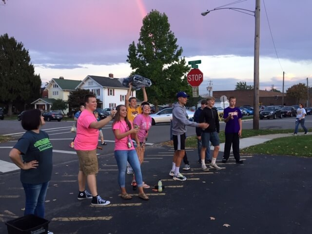 Students playing corn hole in the streets.